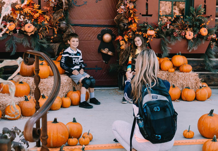 mom taking photo of her kids with pumpkins