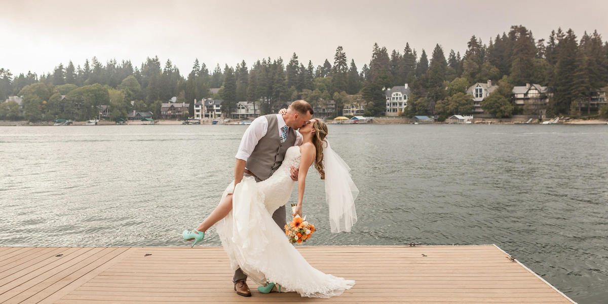 Bride and groom kissing on a dock near the lake